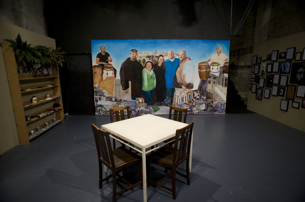 The mural featured here depicts the story of the Jimenez family and their relationship to the Mission district of San Francisco. The mural was created through a participatory process with the Jimenez family and in dialogue with the play, Mirrors in Every Corner. The mural was visible as the backdrop of the stage until the play began. The painting includes historical photos, text from interviews with family members, and media archives depicting struggles against displacement. Photo by Michael Allen Jones.