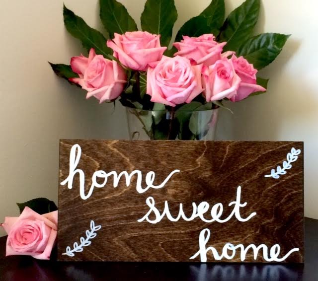 wood sign with white lettering and pink roses