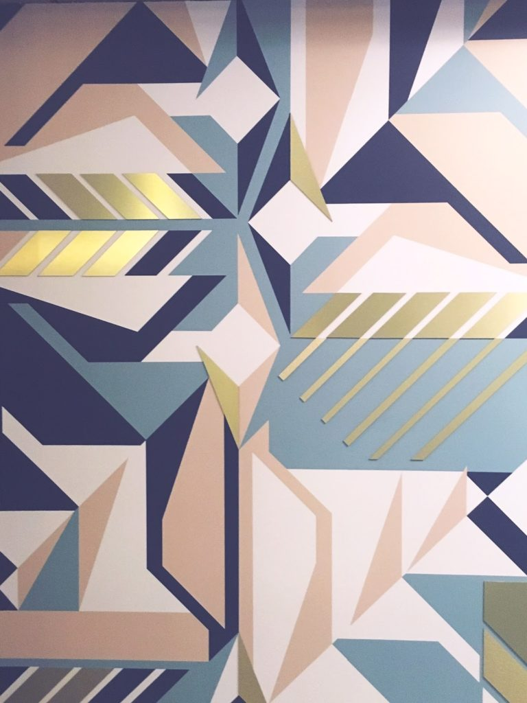 Pink blue and gold geometric designs on wall