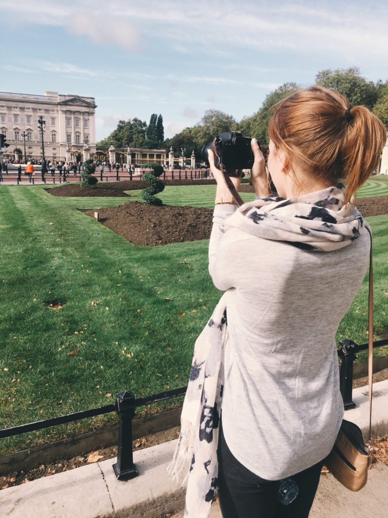 Photographer capturing tourists in front of Buckingham Palace
