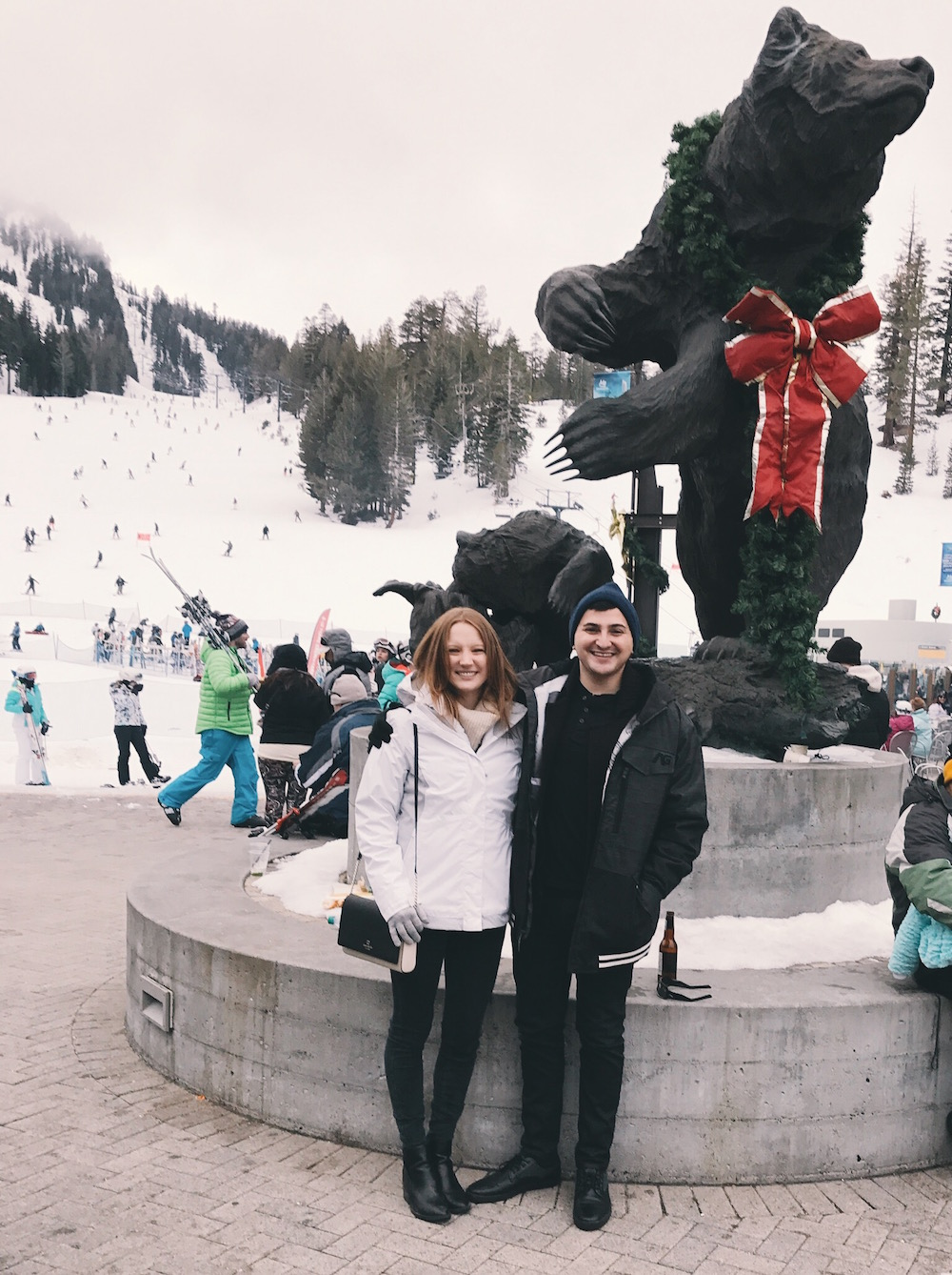 Brooke Christy and David Corcos next to bear statue on mountain