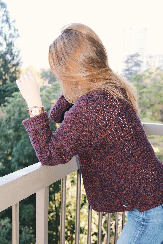 Girl in burgundy sweater wearing wood watch