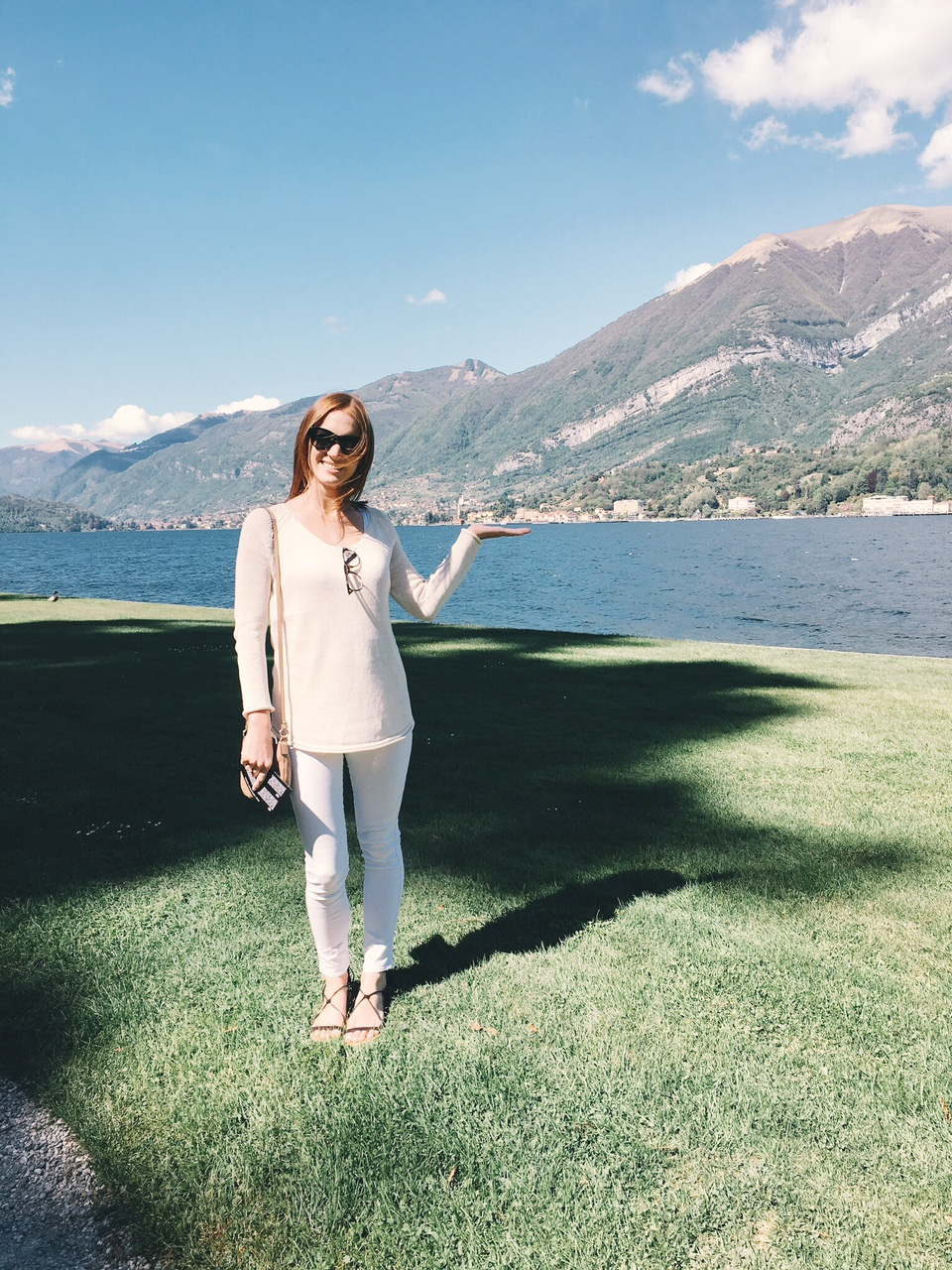 Girl in tan sweater and white jeans sunglasses holding Lake Como Tremezzo from gardens