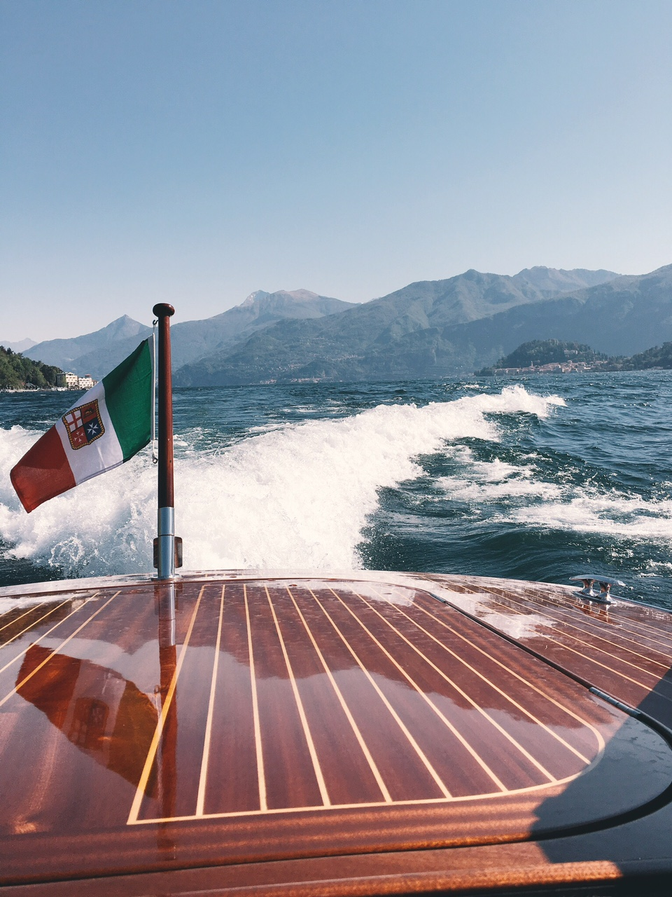 Boat water limousine traveling across Lake Como Italian flag