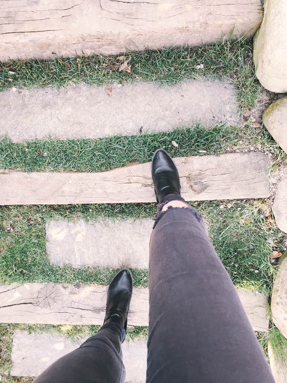 Black jeans ripped knee and black booties walking up wood and grass stairs