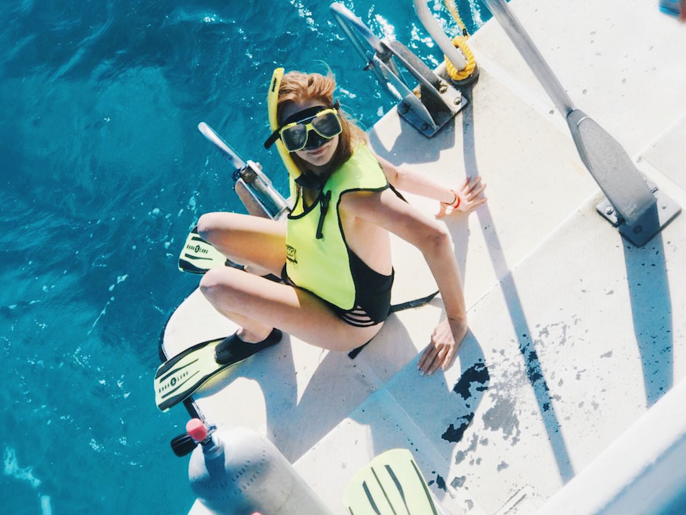 Girl at end of boat getting ready to snorkel mask fins