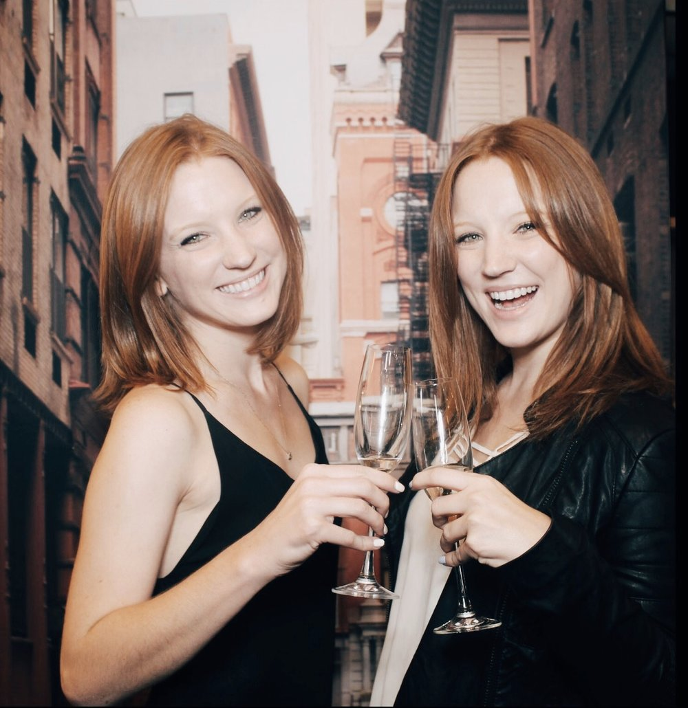 Twin girls red hair toasting champagne glasses in front of new york city backdrop