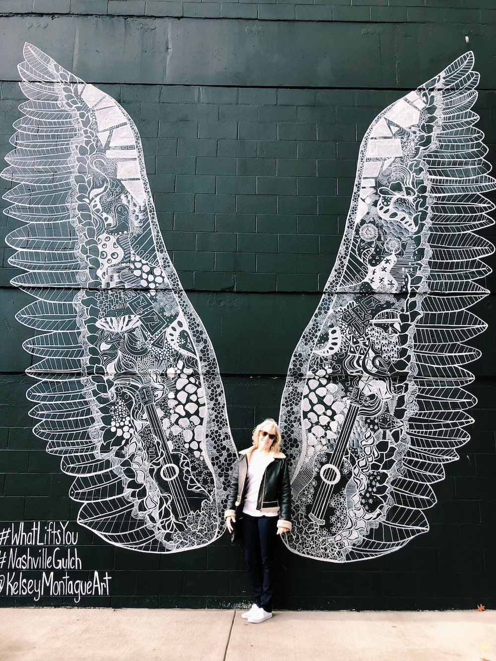Woman in front of black and white wing mural