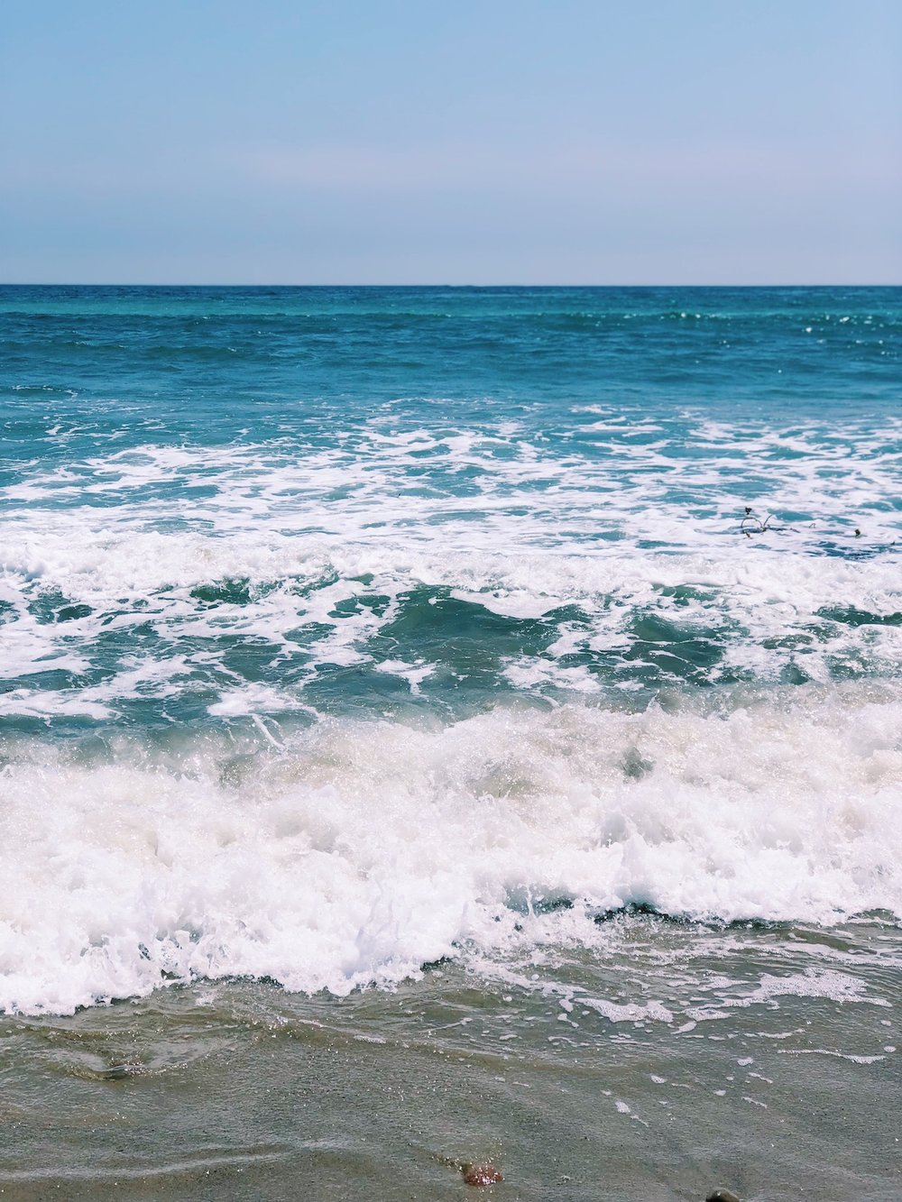 Ocean wave breaks on sand