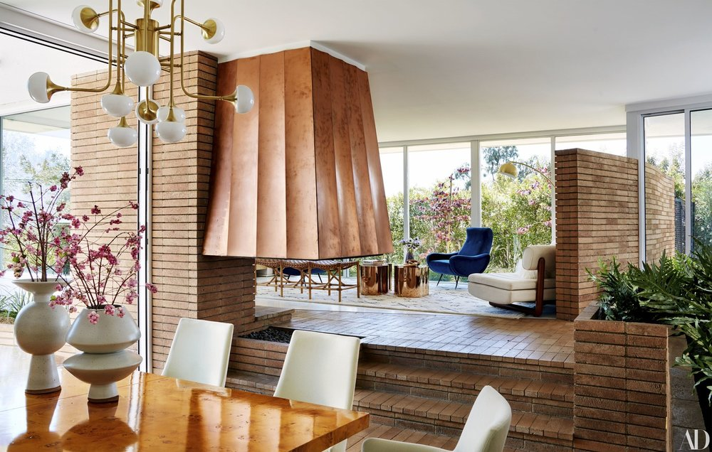 Another view of the front room shows the unique fireplace with its original copper hood that the design team restored to it's glory.
