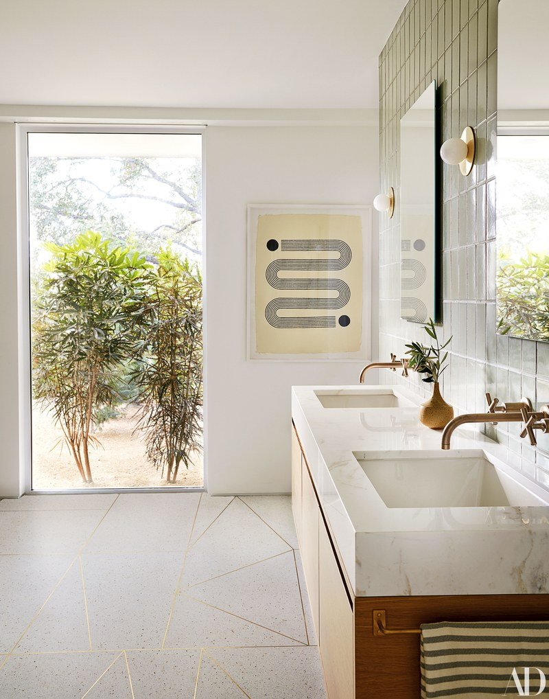 This bathroom has the flooring of our dreams! Love the custom brass inlay set in terrazzo & the volakas marble-topped vanity.