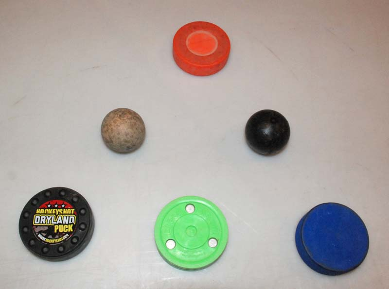 Various stickhandling objects are available. The Dryland Puck (bottom left) costs $12 and is purported to be viable on a sliding surface or floor. In my opinion, it performs poorly in both settings. The Green Biscuit, which sells for about $13, slides okay on a slippery surface but feels heavier and clunkier than a puck on ice. The blue puck ($2) is like a regular puck except it's two ounces lighter. It works fairly well on a shooting pad.The Swedish Ball ($4, second row, left) is a very lightweight wooden ball that really flies around a shooting pad. It's good for working on quick hands. The Extreme Stickhandling Ball ($9,second row,right)is heavy and hard. Surprisingly, on a shooting pad it has a feel similar to a puck on ice. The basic orange floor hockey puck ($2),slides nicely on a floor or shooting pad.