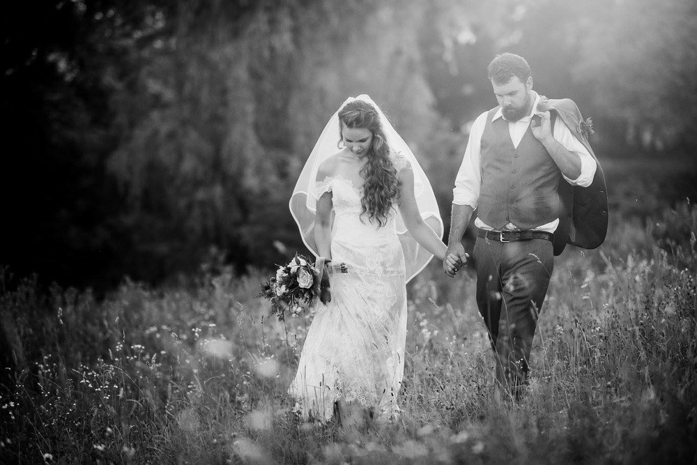 bride and groom walking in field