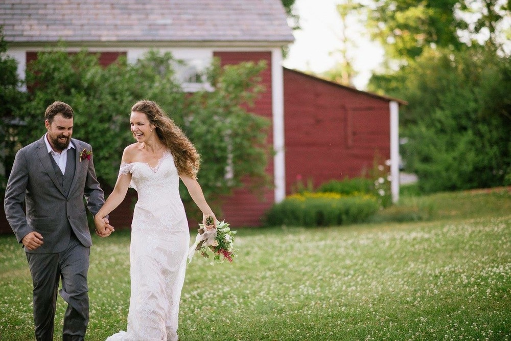 nh bride and groom running in red barn
