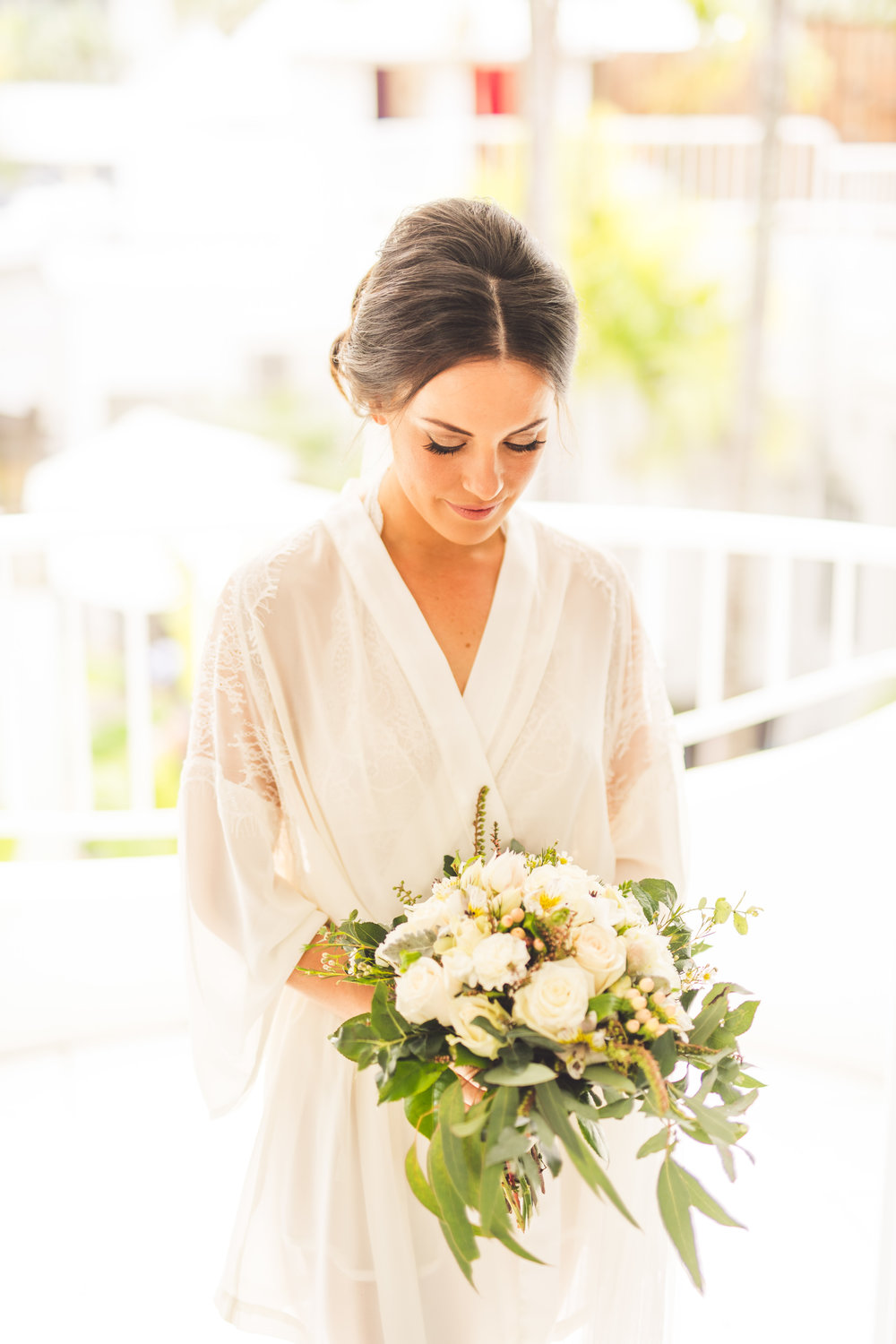 bride looking at greenery bouquet
