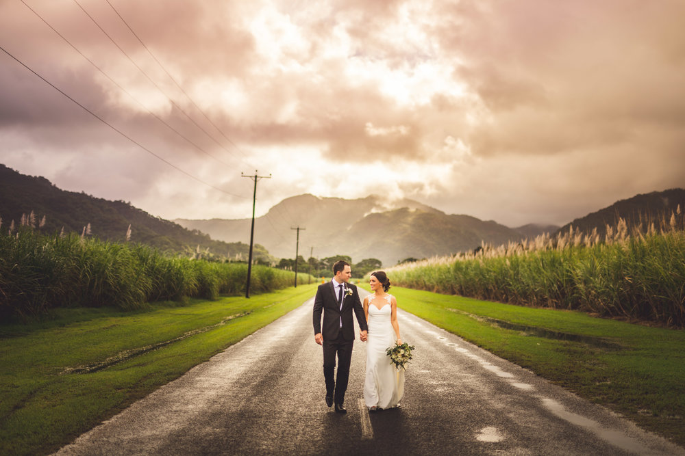 mountain sunset with bride and groom in middle of road