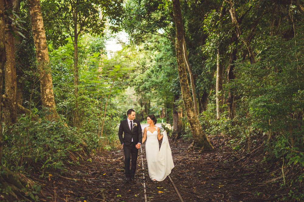 bride and groom on palm cove railroad tracks