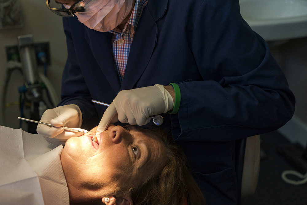 """Dr. Johns has made the claim many times that he """"has retired from dentistry"""". Anyone who knows him knows that this is far from the truth. While he may have retired from his own practice, he can still be found performing a procedure or two at his old office. Here he is, doing some repair works on his wife Rose."""
