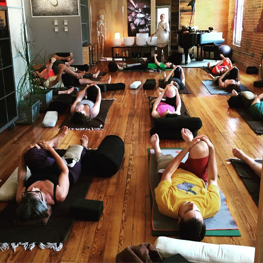 yoga students practicing in durham yoga studio with wood floors,  crystal sound bowls and yoga props