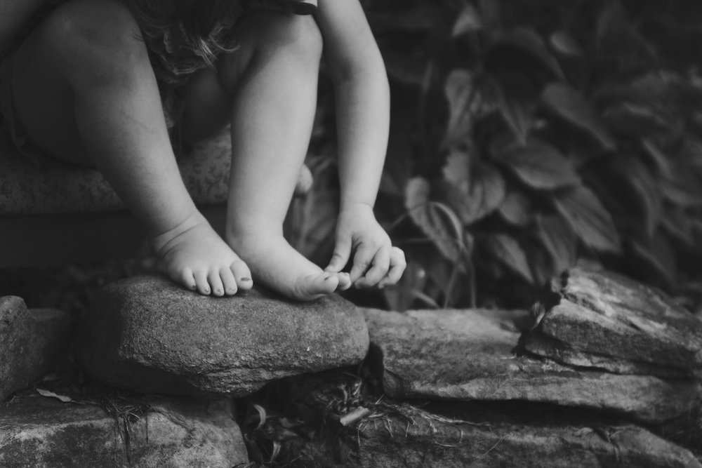 child sitting on rocks playing with toes
