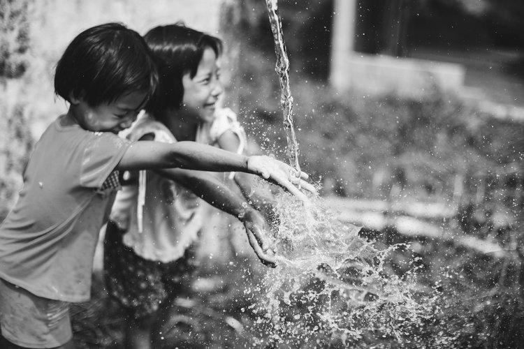 two happy children playing in water