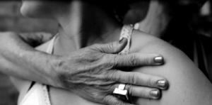 yoga teachers hands of compassion on shoulder