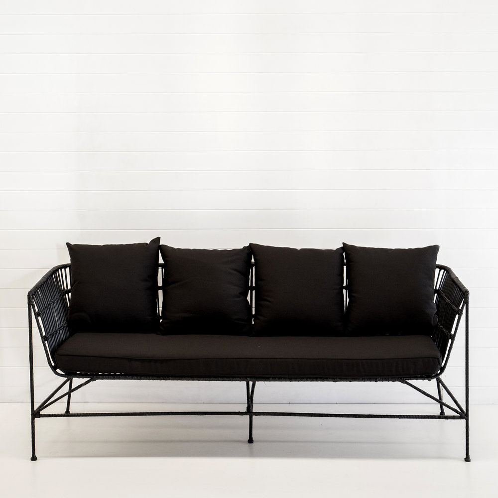 Indie black 3-seater sofa with black cushions