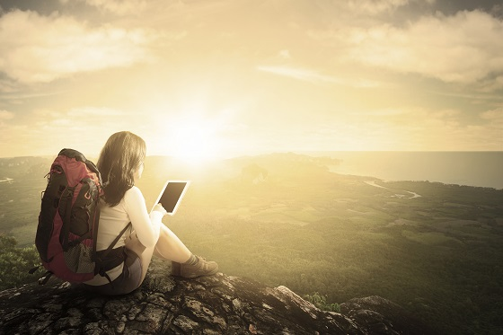 woman on a mountaintop reading a tablet