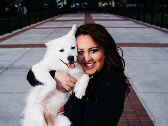 Portrait of a young woman holding her dog, an American Eskimo, in the park-taken by Samgold Photography