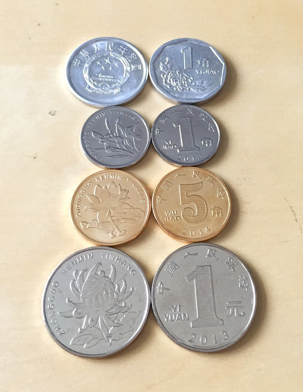 The coins of China. First coins are still 1 cent, but an older version and also made of a different material, feels like aluminum. Coins are 10 cents, 50 cents, and 1 Rmb. Although they are marked as 1 jiao, 5 jiao, and 1 yuan. The flower also seems to grow based on the value of the coin.