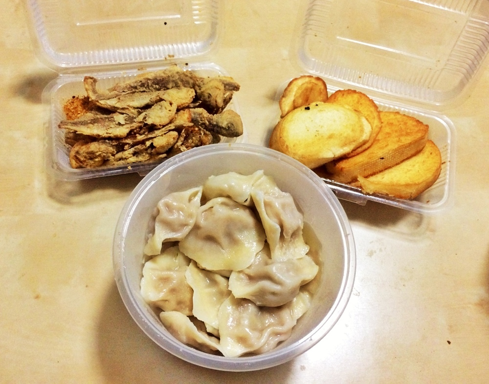 Chinese takeout: dumplings, whole fried fish, and a garlic bread type thing