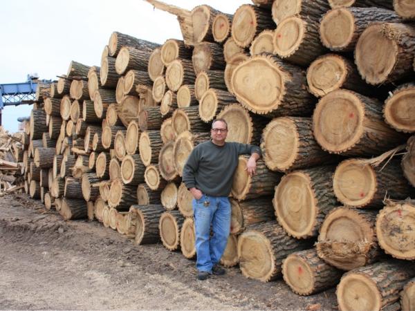 Barton Barcel standing next to a stack of Cottonwood logs at the Mill in Bellwood, Neb.