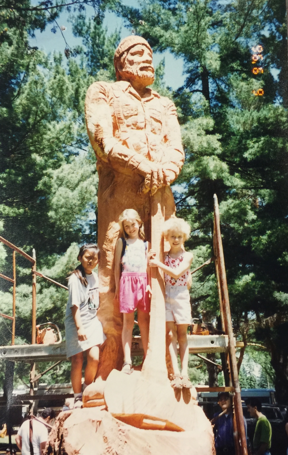 In 1996 Barton and Paula Barcel commissioned Steve Blanchard for a chainsaw carving of a Lumber Jack out of a Redwood log.  They brought the log in from Carmel, CA and its estimated weight was over 7 tons. Their two daughters and a family friend pose with the sculpture while it was on display at the 1996 Antique Tractor Show at Pawnee Park in Columbus, NE.