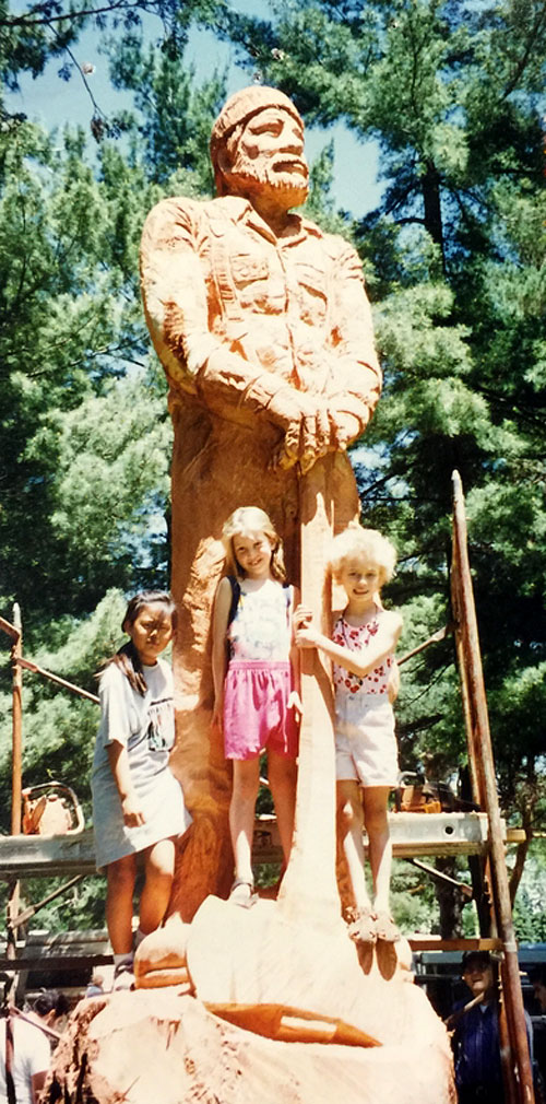 Redwood tree 'Lumber Jack' - In 1996, Barton and Paula Barcel commissioned Steve Blanchard for a chainsaw carving of a Lumber Jack out of a Redwood log. They brought the log in from Carmel, CA and its estimated weight was over 7 tons. Their two daughters and a family friend pose with the sculpture while it was on display at the 1996 Antique Tractor Show at Pawnee Park in Columbus, NE.