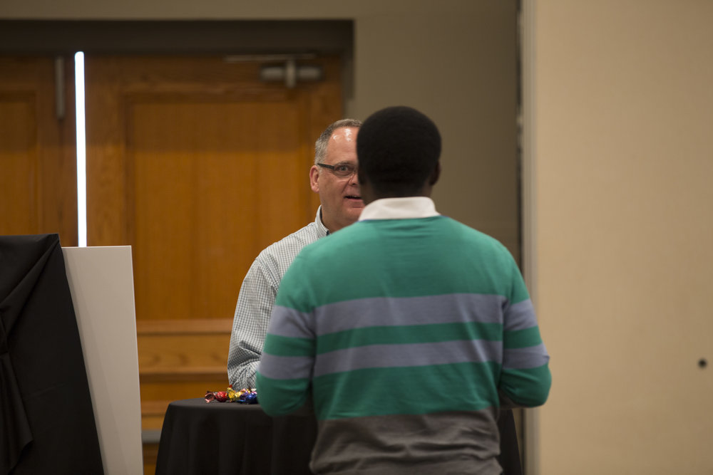 Professor David Chidly giving advice to recent graduate local photographer Bisi Alawode during the Syrian Refugee Exhibition on Friday,November 4,2016, at Lambton College Residence, Sarnia (ON) (Raspal Singh/ David Chidly)