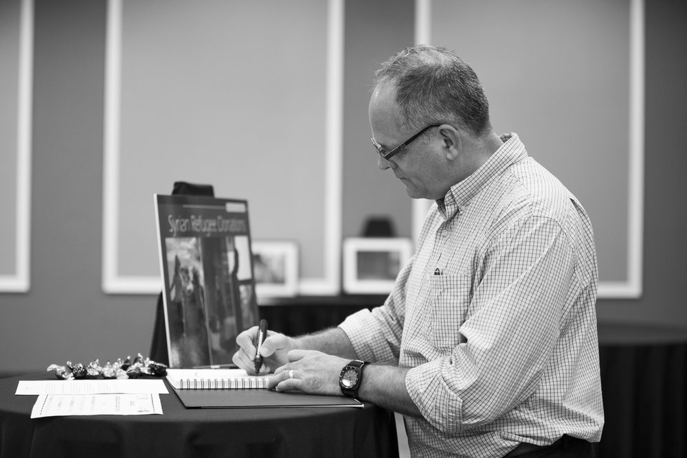 Professor David Chidly signing the thank you note in the book for photography graduate local photographer Bisi Alawode during the Syrian Refugee Exhibition on Friday, November 4, 2016, at Lambton College Residence, Sarnia (ON) (Raspal Singh/ David Chidly)