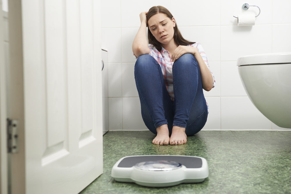 Unhappy-Teenage-Girl-Sitting-On-Floor-Looking-At-Bathroom-Scales-000074105099_Full.jpg
