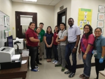 SystemOne Support Specialist Victor Lubuku (light blue shirt) during a GxAlert implementation in the Philippines, with staff from ministry and funder organizations.