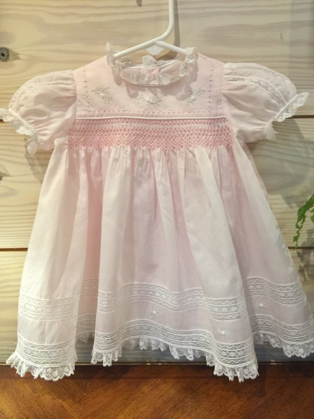 Handmade heirloom baby dress with matching slip and bloomers.  Patty used the finest Swiss batiste, french laces and mother of pearl buttons.  Embroidery and smocking are delicately finished in pink and white.   Handmade sewn and donated by:  Patty McAnally