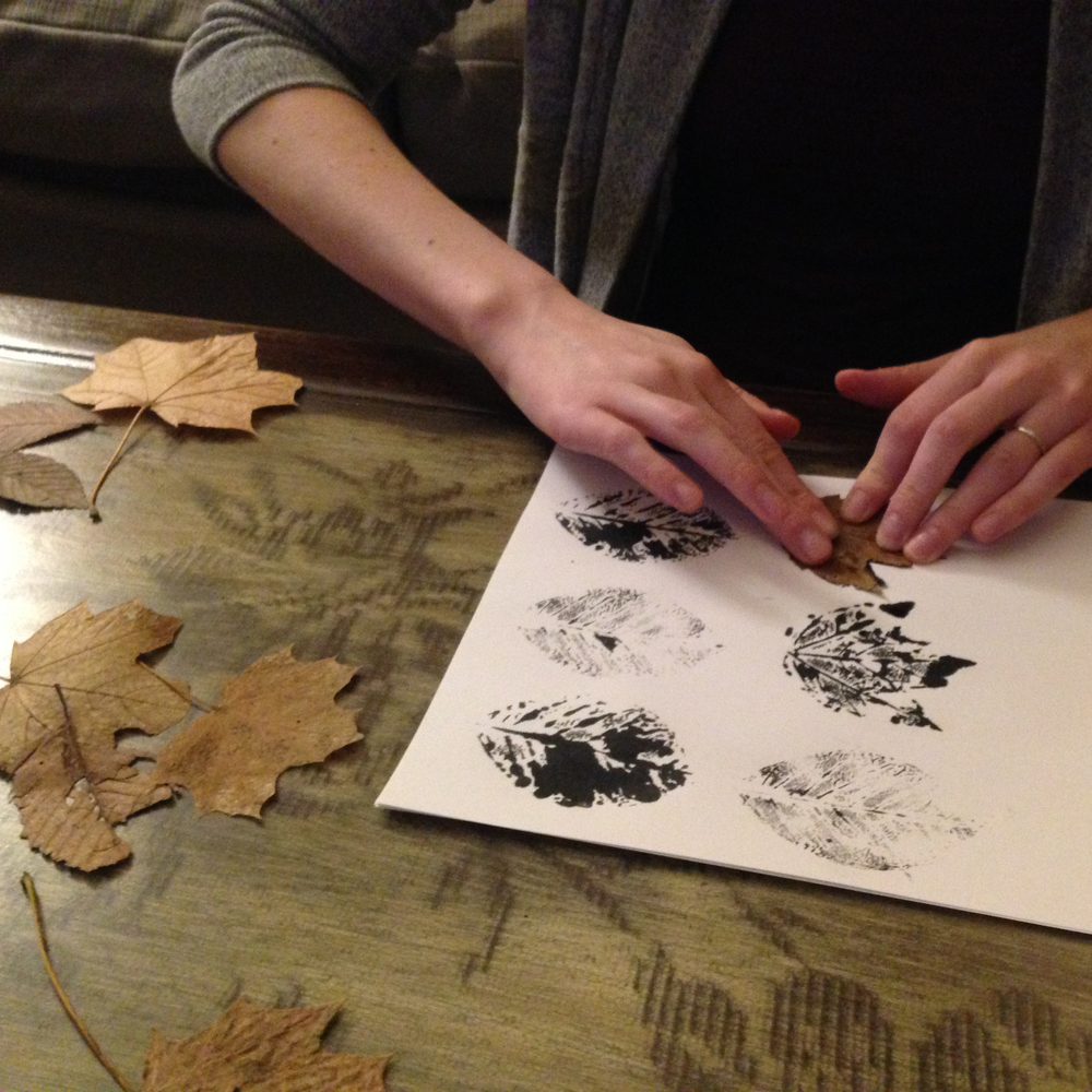 Pressing ink soaked leaves into paper to make an impression.