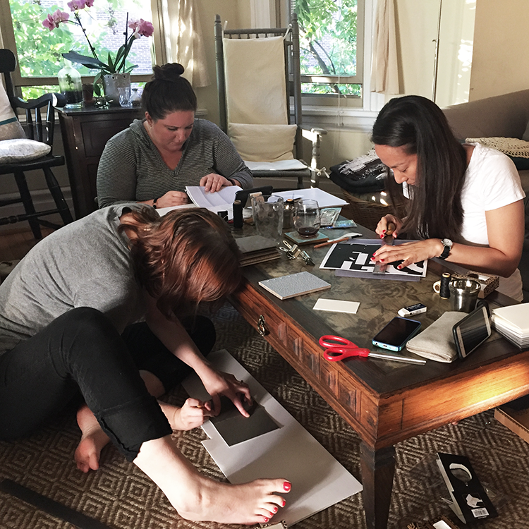 Anna Filbert, Lauren Meranda, and Alice Lee working on their bookbinding coptic stitch books at our living room coffee table and carpet.