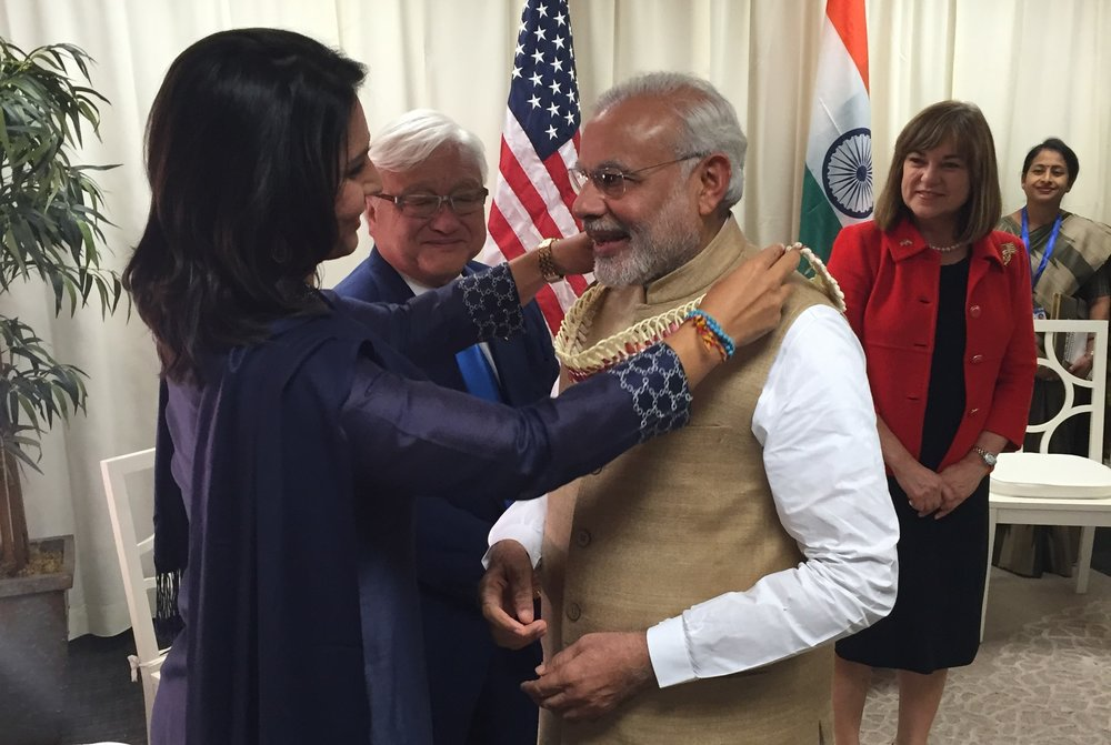 Tulsi Gabbard is seen here embracing and placing a garland over Narendra Modi. Modi was banned from entering the US for his role in persecuting Christians and carrying out the mass murder of Muslims in India.