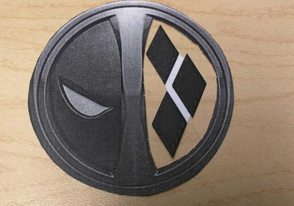 This is where I cut out the printed logos, cut one side out of Deadpool, and replaced it with the Harley logo. This was my template for what I was going for.