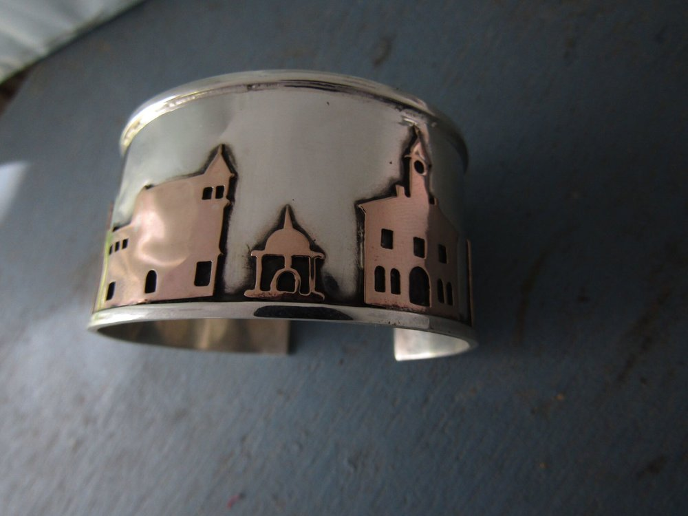 A one-of-a-kind sterling silver cuff bracelet with historic Harrisonburg buildings in bronze relief.