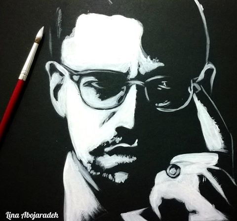 Image Description: A red, wooden small-tipped paint brush with some white paint on tip hovers over a white-on-black painting of Malcom X.  Malcom has a serious look peering out through his glasses, and a finger to his temple as if in deep thought, or trying to project his thought to the object of his gaze.. This painting is a creation of Lina Abojaradeh, her signature is on the bottom left, in white.