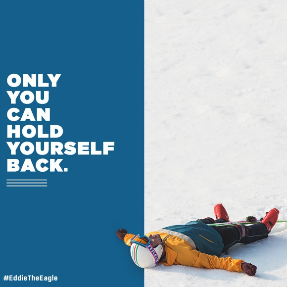 "Photo Description: Left half of photo is blue with the words ""ONLY YOU CAN HOLD YOURSELF BACK."" In the bottom left reads #EddieTheEagle. The right half of the photo is of a snowy ground, a man lays at the bottom of the image wearing full ski gear, looking as if he is about to make a snow angel."