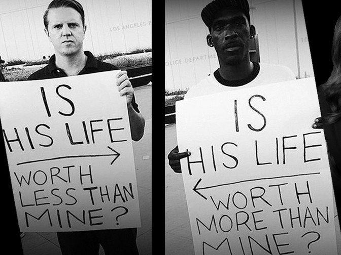 "Photo Description: Two photographs, side-by-side.  On the right is a dark-skinned man with a look that seems to say he is used to this.  Serious, but almost bored.  In his hands is a sign ""IS HIS LIFE WORTH MORE THAN MINE?"" On the sign, there is an arrow pointing to the man on the left.  On the left is a light-skinned man with a look of anger and disgust.  He looks like he wants to hit something.  He also holds a sign ""IS HIS LIFE WORTH LESS THAN MINE?"" On the sign there is an arrow pointing to the right"