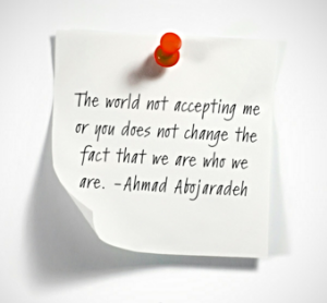"Image Description; A white square post-it-style note with a red thumbtack is stuck into a white wall with Ahmad Abojaradeh's quote on it, ""The world no accepting me or you does not change the fact that we are who we are."""