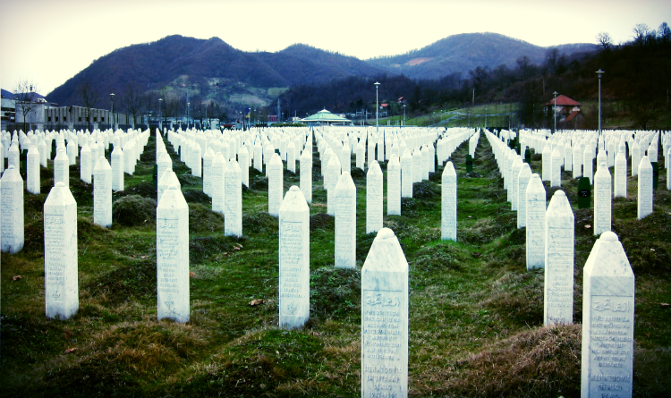 Photo Description: An image of hundreds of white pillar/prism-shaped tombstones with Arabic written on them. They stretch back in a geometric pattern, depending on from where you are looking at them. Some buildings stand on the horizon before mountains rising into a grey sky.