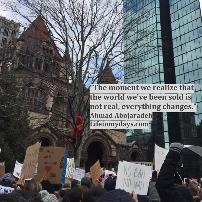 """Photo Description: A group of protestors gather in Copley Square in Boston. They carry signed 'NO BAN NO WALL"""" """"ALL ARE WELCOME"""" and others. Hovering above them is the quote """"The moment we realize that the world we've been sold is not real, everything changes."""""""